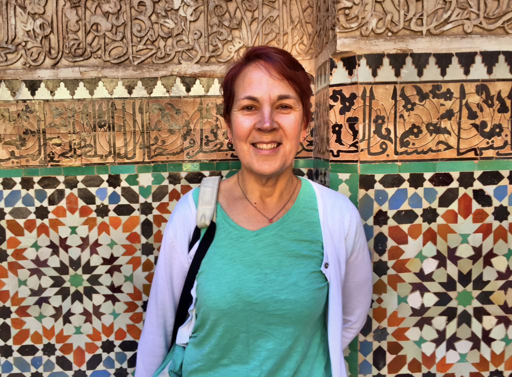 Jenny in front of grand tiles and plaster work in the medersa