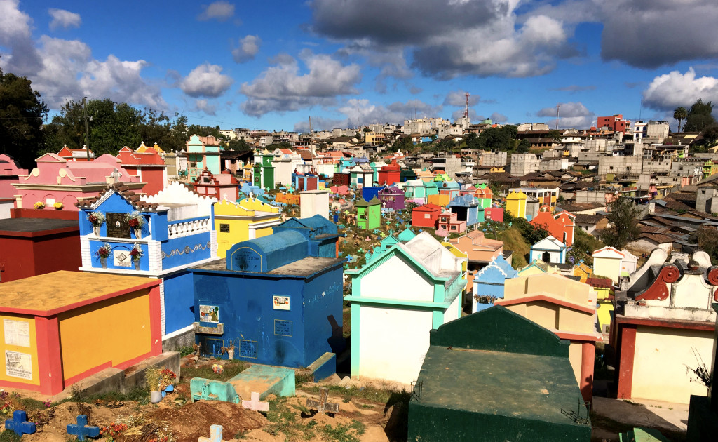 Chichi's brilliant, colorful market is an unexpected counterpoint to the sobriety usually associated with cemeteries. Note how somber the grey buildings of the town are in the background.