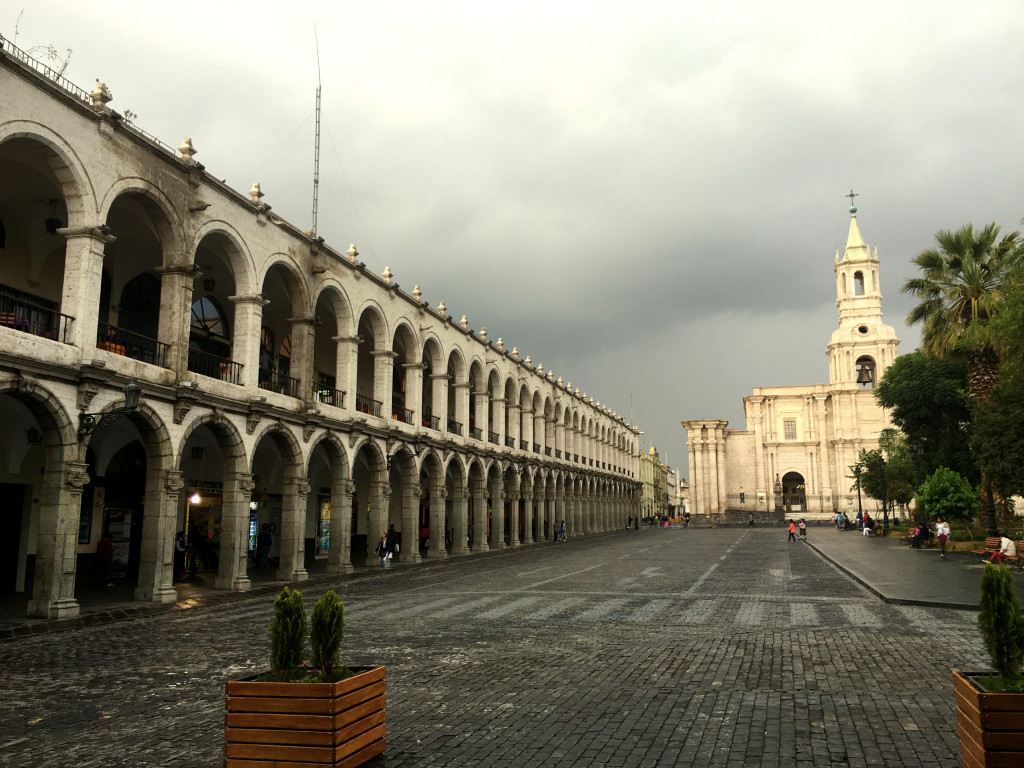 One of the sillar-constructed buildings running along a side of the central plaza, with part of the cathedral in the background