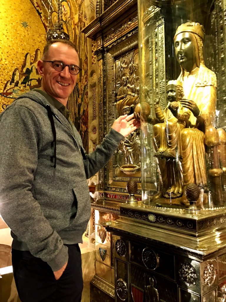 Mark with the venerated Black Madonna. She's behind glass but there's a cutout so you can touch her hand. I think he's blessed now, or something like that.